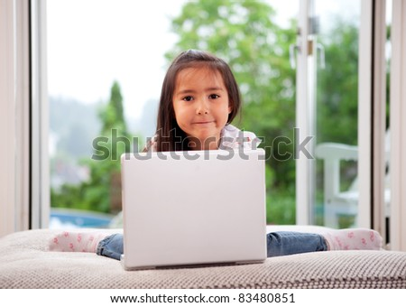 A young child using a laptop computer, sitting on a couch cushion - stock photo