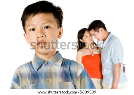 A young Chinese boy standing in front of his parents on white background