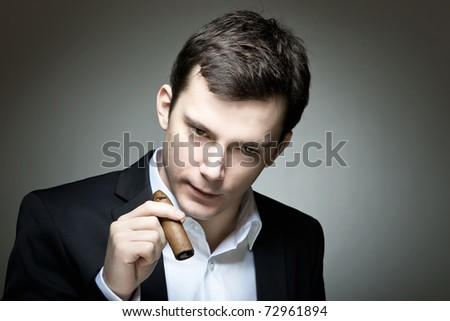 A young cigar smoker in a casual suit
