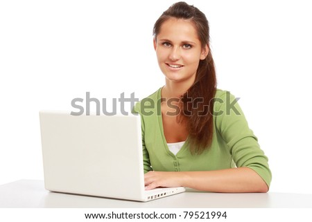 A young college girl sitting in front of a laptop, isolated on white - stock photo