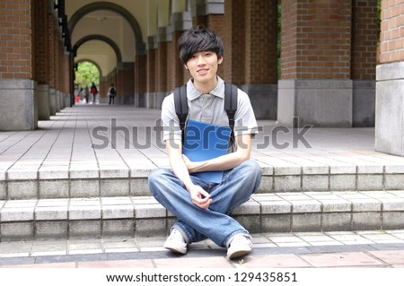 A young college student sitting student reading on campus - stock photo