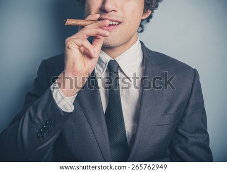 A young confident businessman is smoking a cigar