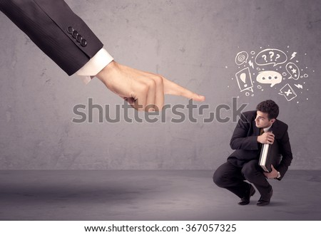 A young confused businessman being fired by large boss hand concept with drawn speech bubbles, exlamation, question marks - stock photo