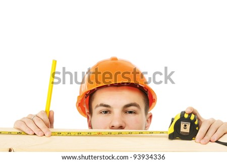 A young construction worker measuring , isolated on white background - stock photo