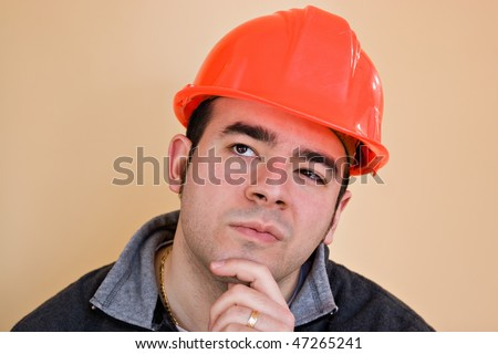 A young construction working with a pensive or contemplative look thinking hard about something.