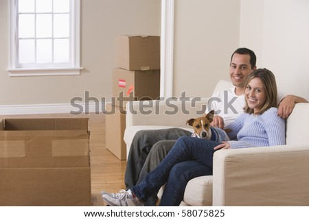 A young couple and their dog are sitting on a couch in a living room. Moving boxes are arranged on the floor around them. Horizontal shot.
