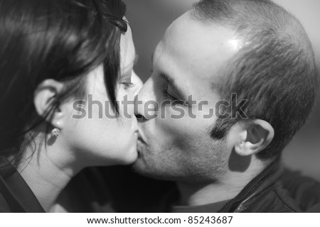 A young couple are kissing - stock photo