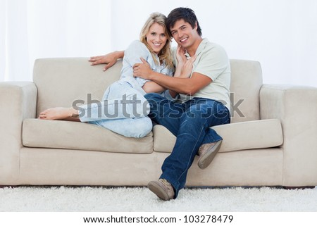 A young couple are sitting down on a couch embracing each other - stock photo