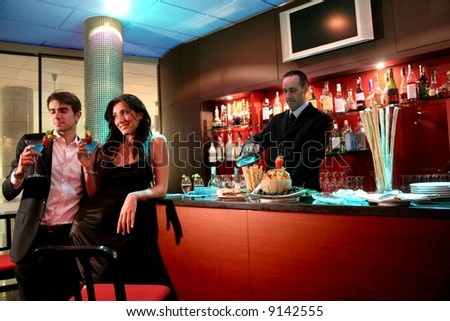 A young couple at bar with cocktails - stock photo