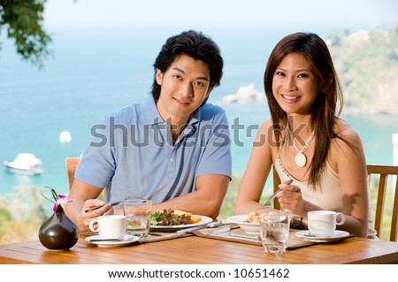 A young couple at breakfast with ocean view behind