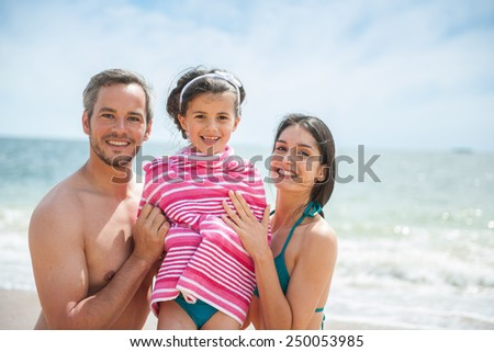 A young couple at the beach is posing in swimsuits with their daughter, Mom and dad are drying their six year old girl with a towel, family looking at the camera.  - stock photo