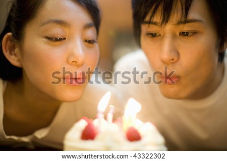 A young couple blowing off birthday candle - stock photo