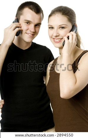 A young couple both using mobile phones on white background - stock photo