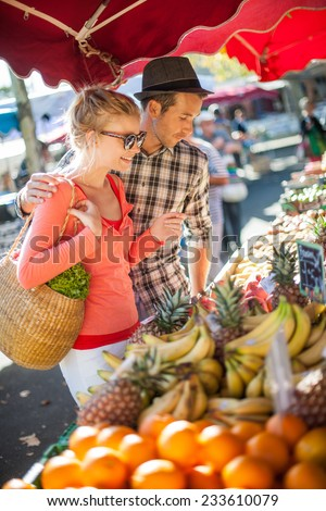 a young couple buying fruits and vegetables in a market on a sunny morning, the young woman carries a basket - stock photo