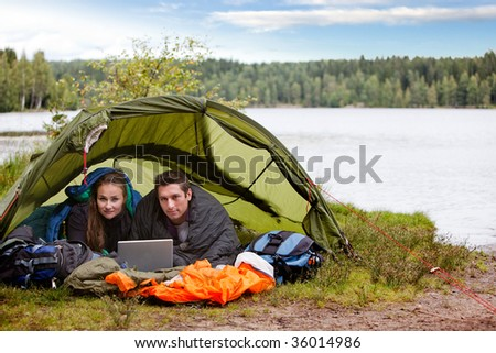 A young couple camping with a laptop near a forest and lake - stock photo