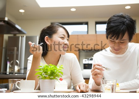 A young couple chatting and eating in the kitchen - stock photo
