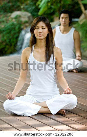 A young couple doing yoga outside - stock photo