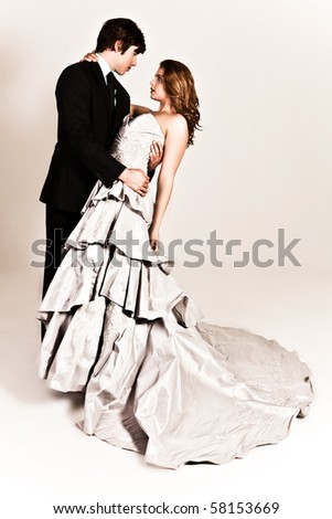 A young couple dressed in formal attire dancing affectionately with the man's arm around the woman's waist. The woman is wearing a white strapless dress and the man is wearing a suit. Vertical shot. - stock photo