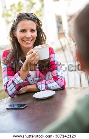 A young couple drinking coffee at cafe - stock photo