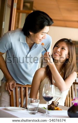 A young couple eating at a restaurant - stock photo