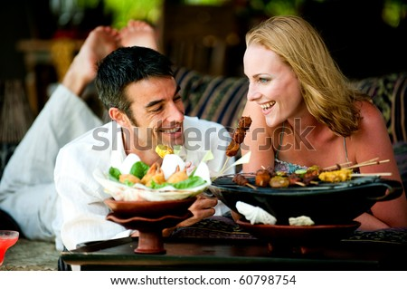 A young couple enjoying a relaxed lunch at a restaurant - stock photo