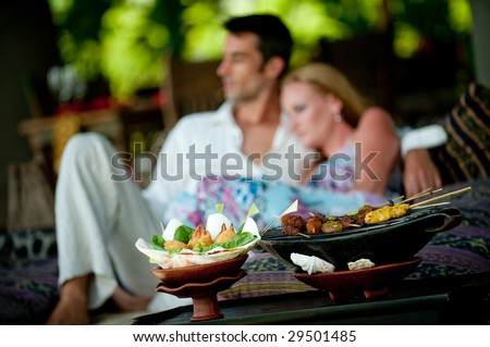 A young couple enjoying a relaxed lunch whilst on vacation (focus on food)