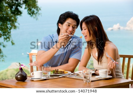 A young couple enjoying breakfast together on vacation - stock photo