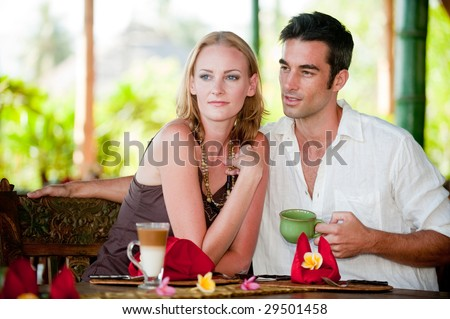 A young couple enjoying breakfast whilst on vacation - stock photo