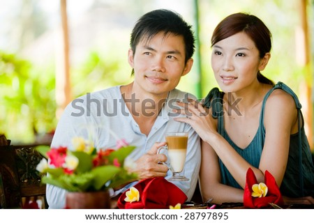 A young couple enjoying morning coffee whilst on vacation - stock photo