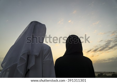 A young couple enjoying the sunset in the desert near Dubai