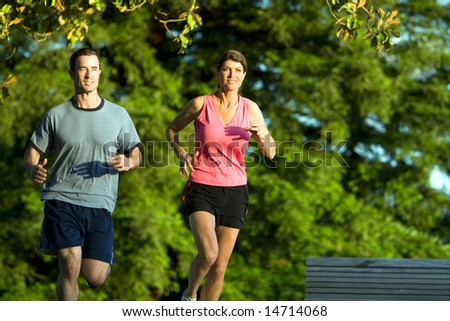 A young couple go jogging around a park with each other, smiling. - horizontally framed - stock photo