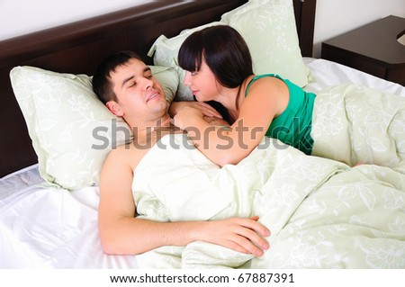 A young couple had just woken up in bed together early in the morning.