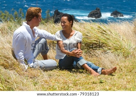 A young couple have a conversation while sitting in the tall grass on a cliffside overlooking the ocean in Maui, Hawaii. - stock photo