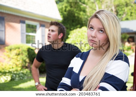 A young couple having a disagreement.  The young lady rolls her eyes at the young man who seems distracted and confused in the background. - stock photo