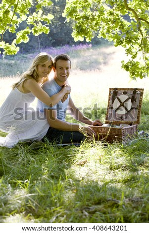 A young couple having a picnic, embracing