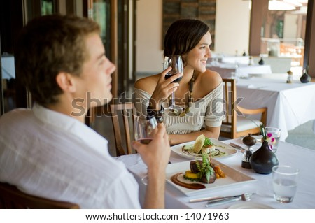 A young couple having dinner at a restaurant - stock photo