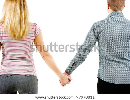 A young couple holding each other's hands. View from the back - stock photo