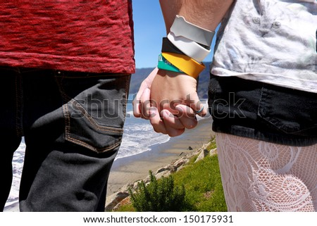 A young couple holding hands and looking over a beach view from a hilltop. - stock photo