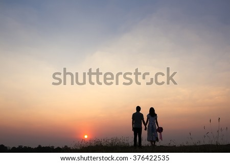 A young couple holding hands. In Nature sunrise, vintage tone - stock photo