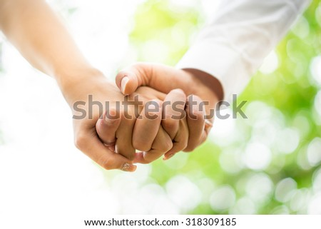 A young couple holding hands in the park, London.