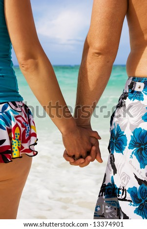 A young couple holding hands on the beach in Cuba - stock photo