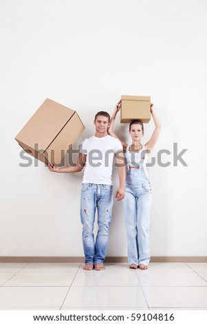 A young couple holds boxes in apartment