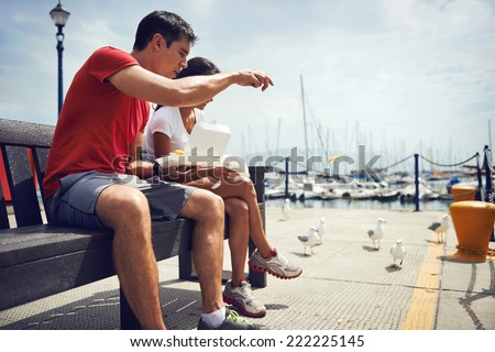 A young couple in fitness clothing eating take away fish and chips by the harbour with seagulls beside them - stock photo