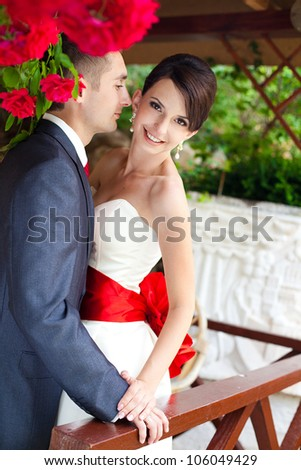 A young couple in love bride and groom with a bouquet, posing in their wedding day. Enjoy a moment of happiness and love. - stock photo