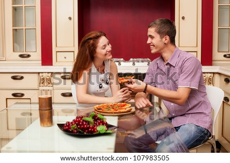 a young couple in love eating pizza - stock photo