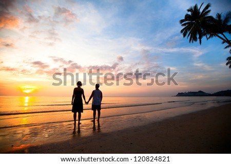 A young couple in love holding hands at sunset at the seaside - stock photo