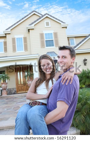 A young couple in love in front of their new home (Focus on Woman) - stock photo