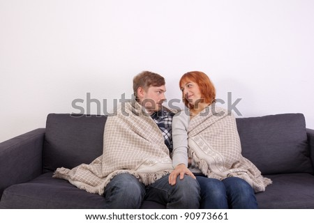 A young couple in love is sitting on the couch