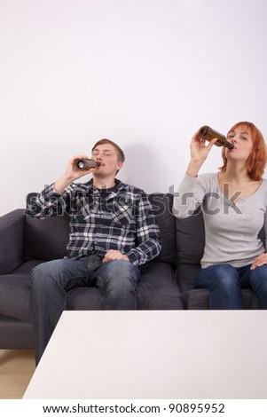 A young couple in love is sitting on the sofa and drinking beer