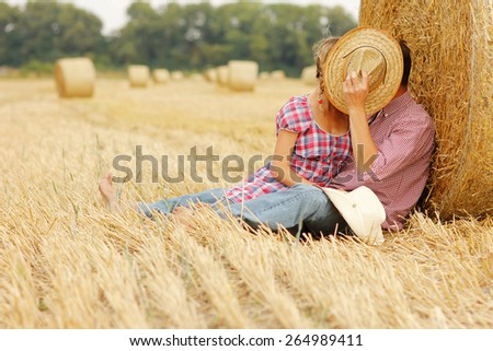 a young couple in love on haystacks in cowboy hats - stock photo